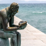 Build Participation: Image is sculpture of man thinking on a dock.