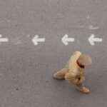 Limitless Leadership Success: Image is person walking opposite to arrows printed on the road surface