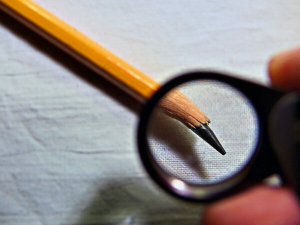 Human Trust Breakers: Image is Magnifying glass looking at broken pencil point.