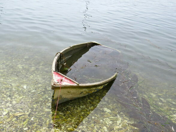 Uncaring Workplace: Picture is a half ditched row boat.